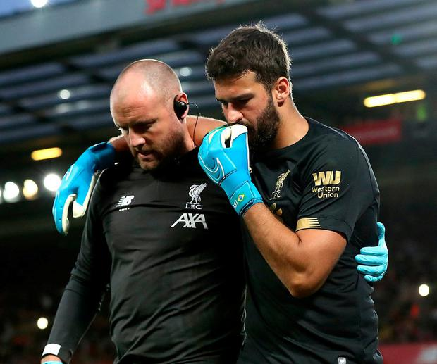 Liverpool goalkeeper Alisson leaves the pitch after picking up an injury. Photo: Martin Rickett/PA Wire