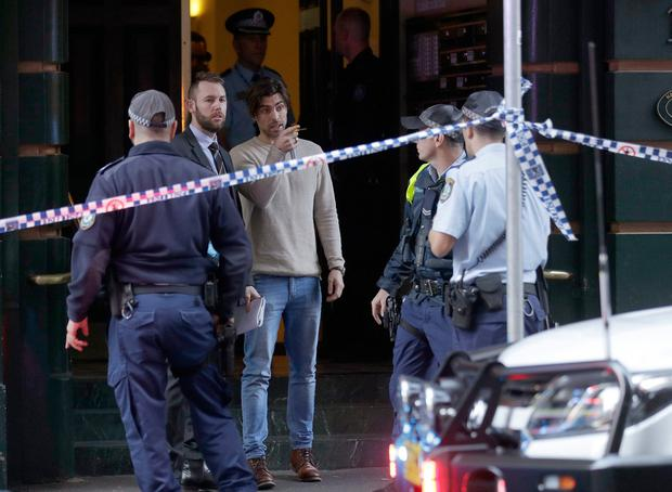 A man, center, points as he assists police at a building where a person has been found deceased after a man attempted to stab multiple people in Sydney, Australia, Tuesday, Aug. 13, 2019. (AP Photo/Rick Rycroft)