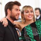 Miley Cyrus (R) and Liam Hemsworth arrive for the 2019 Met Gala at the Metropolitan Museum of Art on May 6, 2019, in New York. - The Gala raises money for the Metropolitan Museum of Arts Costume Institute. The Gala's 2019 theme is Camp: Notes on Fashion