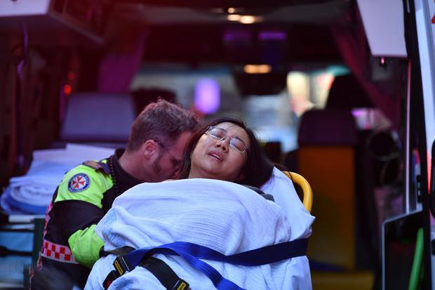 Safe: An injured woman is taken away by ambulance. Photo: Dean Lewis/AAP/via REUTERS