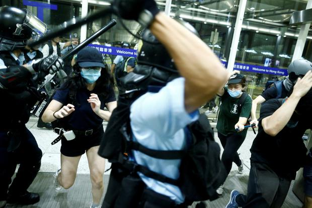 Police clash with anti-government protesters at the airport in Hong Kong, China, August 13, 2019. REUTERS/Thomas Peter