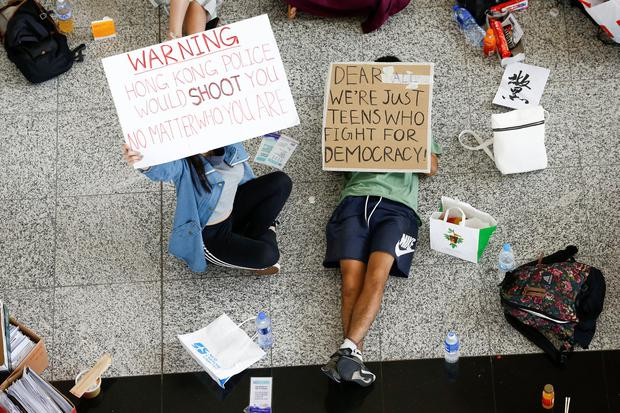 Anti-government demonstrators sit in a designated area of the arrival hall of the airport, after police and protesters clashed the previous night, in Hong Kong, China August 14, 2019. REUTERS/Thomas Peter