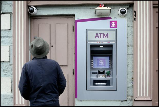 A local passerby takes a closer look at the scene of the ATM foiled raid on the Main Street in Virginia, Co Cavan. Pic Steve Humphreys