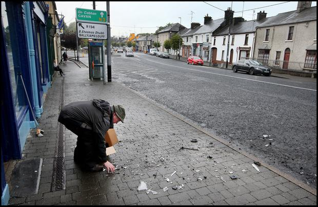 Ray Arnold cleans up the damage across the road from the scene of the ATM foiled raid on the Main Street in Virginia, Co Cavan. Pic Steve Humphreys