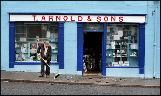 Ray Arnold cleans up the damage across the road from the scene of the attempted raid in Virginia, Co Cavan. PHOTO STEVE HUMPHREYS
