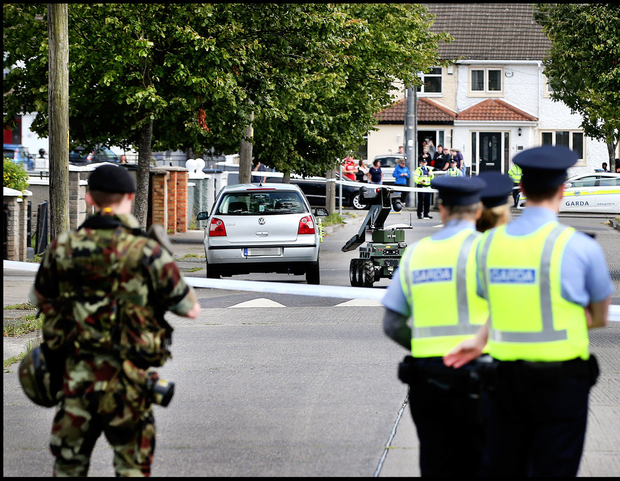 High alert: Gardaí and army bomb disposal personnel monitor the robot as it approaches a VW car in Coolock, Dublin
