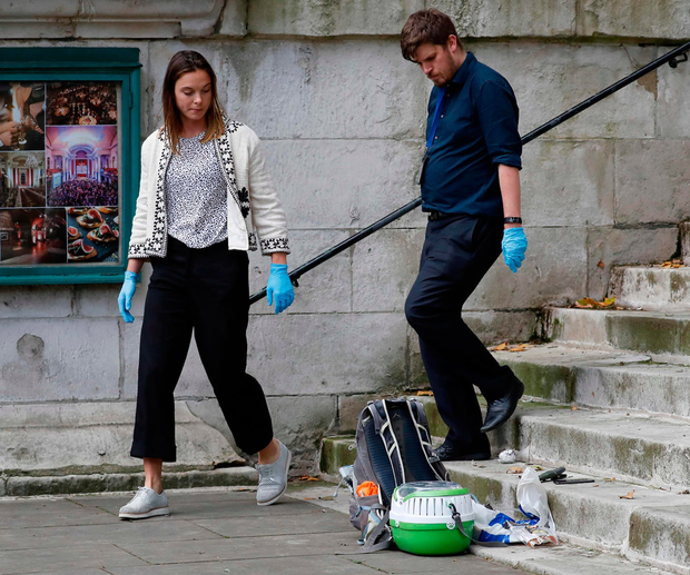 TOPSHOT - British police officers inspect items, including a bag and a sheathed knife, at the former parish church of St John's Smith Square in central London on August 15, 2019 following the arrest of a suspect in connection with a stabbing incident outside the nearby Home Office building. Photo: Tolga AKMEN / AFP