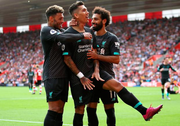 Liverpool's Roberto Firmino celebrates scoring his side's second goal yesterday with team-mates Alex Oxlade-Chamberlain and Mo Salah. Photo: Steven Paston