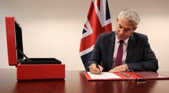 Brexit Secretary Stephen Barclay signs the commencement agreement for Britain to leave the EU. Photo: REUTERS