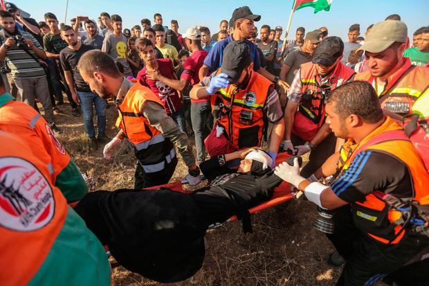 Palestinian paramedics carry a wounded protester during clashes with Israeli forces near the fence along the border with Israel. Photo: Getty Images