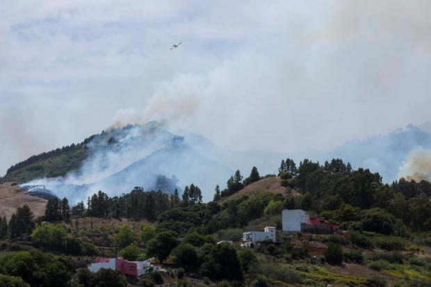 Flames and smoke from a forest fire are seen in the village of Galdar on the Canary Island of Gran Canaria, Spain, August 18, 2019. REUTERS/Borja Suarez