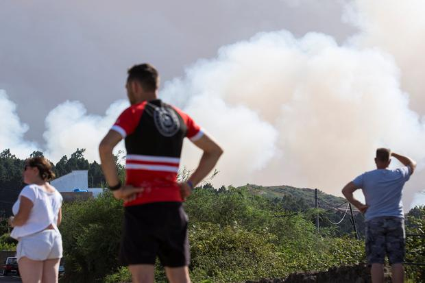 People who were evacuated from their homes look at a forest fire seen in the village of Galdar on the Canary Island of Gran Canaria, Spain, August 18, 2019. REUTERS/Borja Suarez