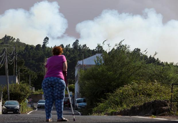 A woman evacuated from her home looks at a forest fire seen in the village of Galdar on the Canary Island of Gran Canaria, Spain, August 18, 2019. REUTERS/Borja Suarez