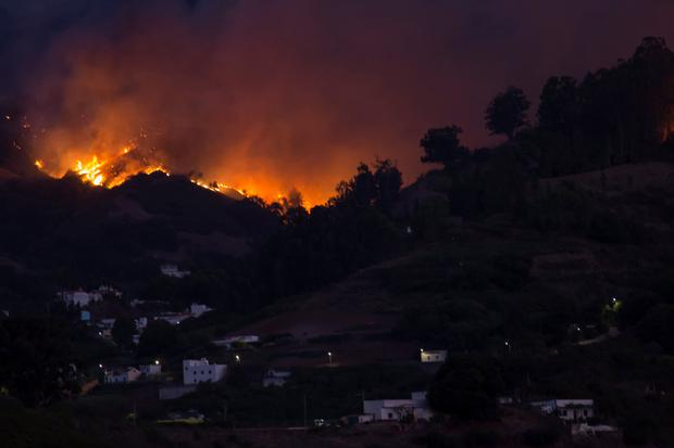 Flames and smoke from a forest fire are seen in the village of Moya on the Canary Island of Gran Canaria, Spain, August 18, 2019. REUTERS/Borja Suarez