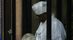 Caged: Sudan's deposed leader Omar Hassan al-Bashir in traditional dress in a cage in court in Khartoum yesterday. Photo: Ebrahim HAMID / AFP