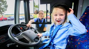 Driving seat: Naoise O'Molloy (5), from Trim, Co Meath, tries on a uniform for size with bus driver Suzanne Armstrong in attendance. Photo: Gareth Chaney, Collins