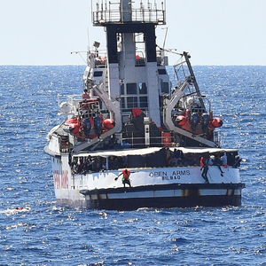 Rescue: Migrants jump from a rescue ship close to the island of Lampedusa. Photo: Reuters