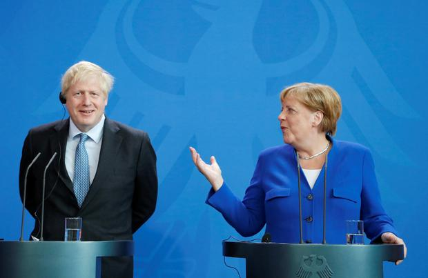 German Chancellor Angela Merkel speaks as Britain's Prime Minister Boris Johnson reacts at the Chancellery in Berlin, Germany August 21, 2019. REUTERS/Fabrizio Bensch