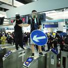 Demonstrators stand on turnstiles during a protest at the Yuen Long MTR station in Hong Kong. AP Photo/Kin Cheung