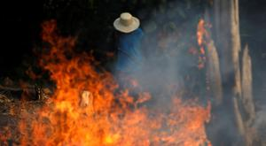 A man works in a burning tract of Amazon jungle as it is being cleared by loggers and farmers in Iranduba, Amazonas state, Brazil August 20, 2019. REUTERS/Bruno Kelly/File Photo