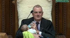 Screenshot from a Parliament broadcast of New Zealand Speaker Trevor Mallard feeding a Member of Parliament's baby during a parliamentary session in Wellington August 21, 2019. New Zealand Parliament and Speaker's Office/Handout via REUTERS