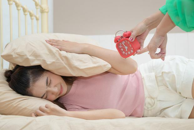 Mother's holding an alarm clock and waking up her teenage daughter at morning