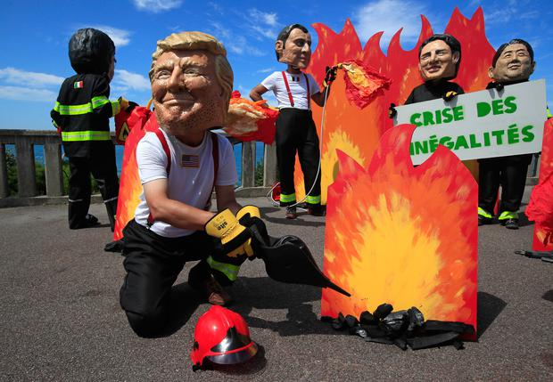 A man wearing a mask President Donald Trump is joined by other 'world leaders' during a protest ahead of the G-7 summit in Biarritz, France Friday, Aug. 23, 2019. (AP Photo/Peter Dejong)