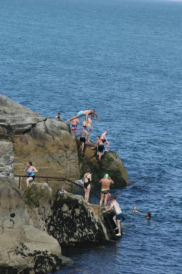 Taking the plunge: Swimmers make the most of the fine weather at the Forty Foot in Sandycove. Picture: Collins