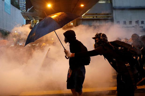 Tear gas floats around demonstrators as they clash with riot police during a protest in Hong Kong, China, August 25, 2019. REUTERS/Tyrone Siu