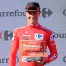 Ireland's Nicolas Roche of Team Sunweb, wearing the leader´s red jersey, celebrates on the podium after the second stage of the 2019 La Vuelta cycling tour of Spain. Photo by JOSE JORDAN / AFP/Getty Images
