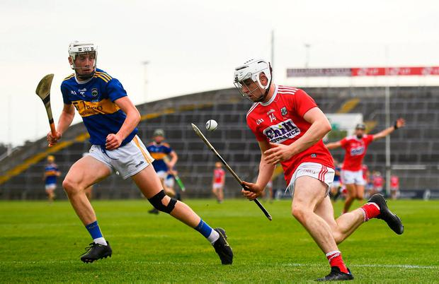 Cork's Shane O'Regan keeps possession up against Eoghan Connolly of Tipperary. Photo: David Fitzgerald/Sportsfile