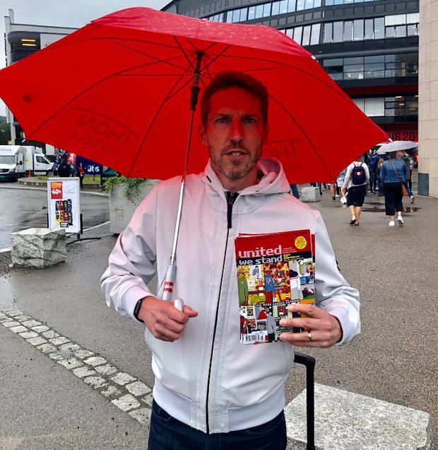 Andy Mitten outside Old Trafford with the 'United We Stand' fanzine