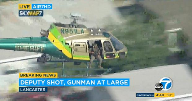 A sheriff's department helicopter with a sniper in an open door searching for a gunman at large in Lancaster, California. Photo: KABC-TV via AP