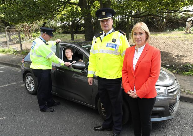 Garda Derek Coackley inspecting the licence of driver Mark Lavery watched on by Moyagh Murdock, RSA CEO and Garda Chief Superintendent Paul Cleary. Photo: Robbie Reynolds