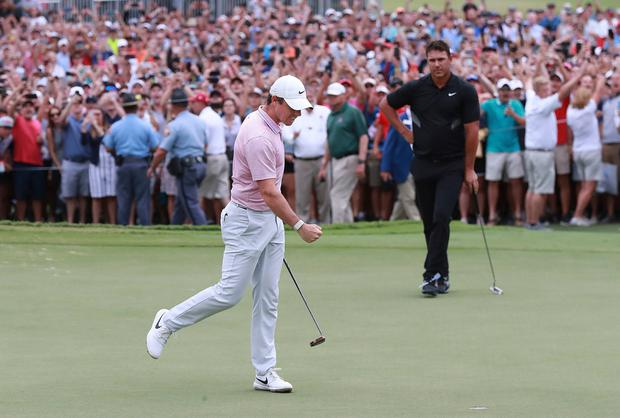 Rory McIlroy pumps his fist, the patrons cheer, and Brooks Koepka looks as as the birdie putt drops to win the Tour Championship golf tournament and The FedEx Cup on Sunday at East Lake Golf Club in Atlanta. Photo: Curtis Compton/AP