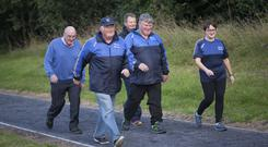 That fitter feeling: Moore Movers exercise group organiser Laura Tully walks with Noel Higgins, Peter Naughton (cap), Martin Greene and Shane Hardiman. Photo: Brian Farrell