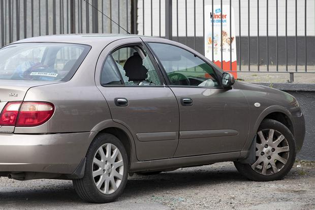 Shattered: The woman owner of the car and her children were just returning when the bullets hit