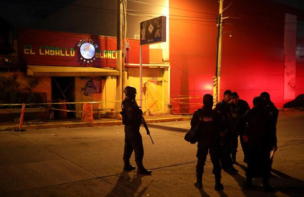 Police officers guard the scene outside a bar where more than 20 people died in an overnight attack. Photo: Felix Marquez/AP Photo