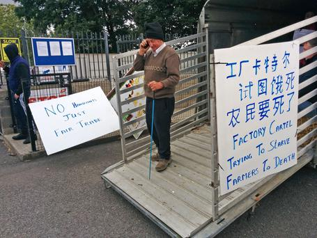 Message: A farmer takes part in a protest at the ABP plant in Bandon, Co Cork, which featured translated signs to greet a Chinese delegation visiting the plant. Photo: Denis Boyle