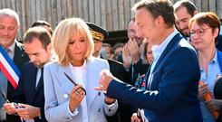 Day in sun: Brigitte Macron and French TV host Stéphane Bern open the Agincourt Historic Centre. Photo: Getty