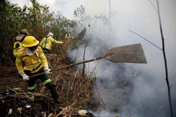 Firefighters work to put out fires along the road to Jacunda National Forest. Photo: AP Photo/Eraldo Peres