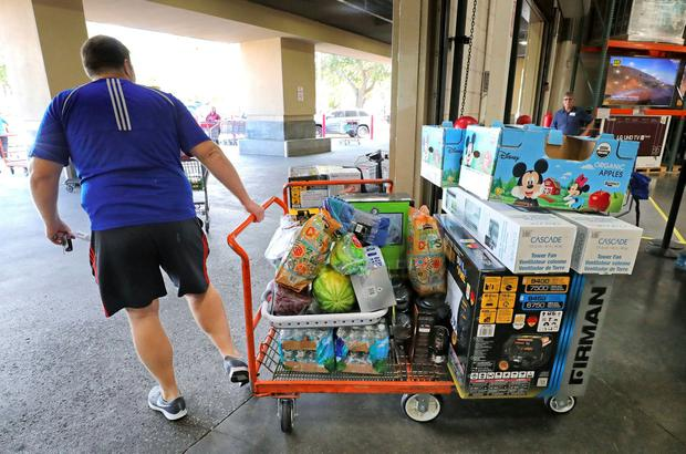 A shopper leaves stocked up, including with a new generator and power fans, at the Costco store in Altamonte Springs, Fla., Friday, Aug. 30, 2019, as central Florida residents prepare for a possible strike by Hurricane Dorian. (Joe Burbank/Orlando Sentinel via AP)