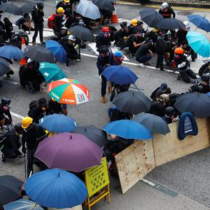 Demonstrators take cover during a protest in Hong Kong, China August 31, 2019. REUTERS/Kai Pfaffenbach