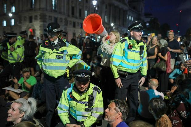 London Metropolitan Police is aiming to shut down an on-going protest through negotiations with dozens of Anti-Brexit supporters who continue to participate in a late evening protest blocking the Houses of Parliament square in central London, Wednesday, Aug. 28, 2019. (AP Photo/Vudi Xhymshiti)