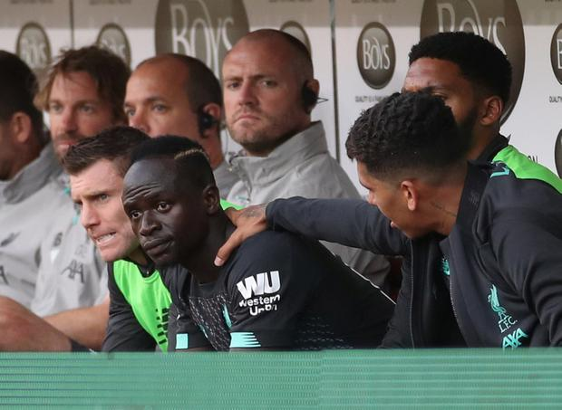 Liverpool's Roberto Firmino places his hand on the shoulder of Sadio Mane as they are sat on the bench after being substituted off