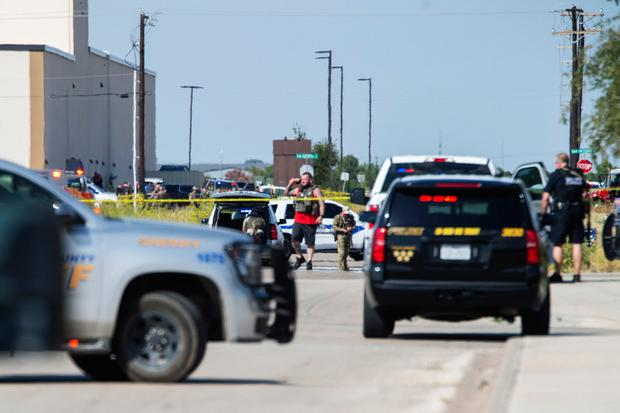 Odessa and Midland police and sheriff's deputies surround the area behind Cinergy in Odessa, Texas, Saturday, Aug. 31, 2019, after reports of shootings. (Tim Fischer/Midland Reporter-Telegram via AP)