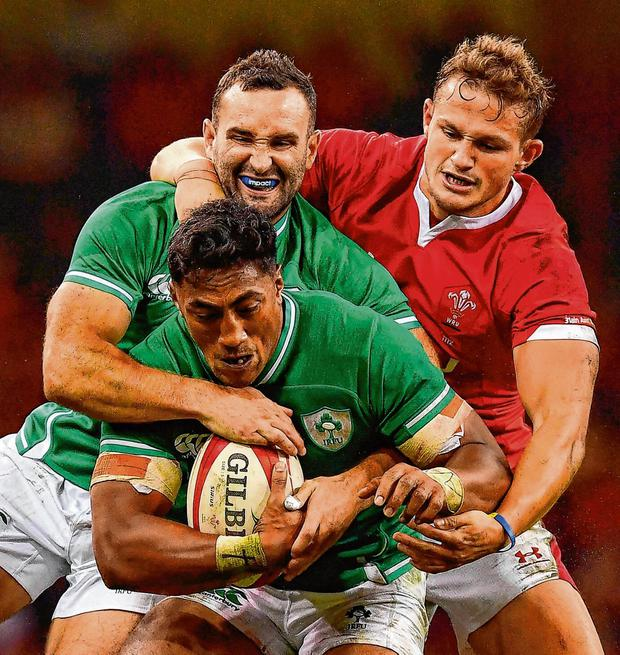 Bundee Aki, supported by Ireland team-mate Dave Kearney, is tackled by Hallam Amos of Wales. Photo: Brendan Moran/Sportsfile