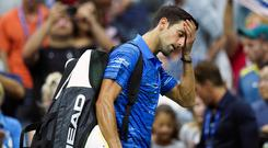 Novak Djokovic walks off the court as he retires during his match against Stan Wawrinka