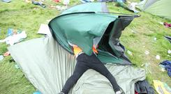All over: A reveller relaxes in a tent surrounded by debris after Electric Picnic. Photo: Collins Photos