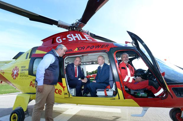 Up in the air: Tánaiste Simon Coveney and Junior Mental Health Minister Jim Daly with John Kearney, founder and volunteer, and John Murray with the charity air ambulance at Rathcoole Aerodrome. Photo: Don MacMonagle